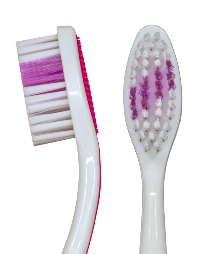 "Closeup of the profile and straight-on views of the Pink ""Selfie"" Standard manual toothbrush from Toothbrushery.com. The brush handle is white with a pink grip on the back. The bristles are white and pink, with the pink portion being a diagonal stripe across the middle of the bristles."