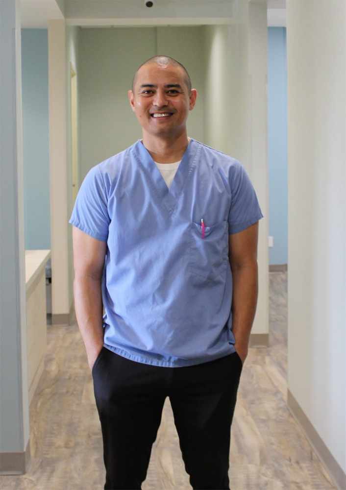 Photo of Tootbrushery.com Founder Patricio Andres, standing in the hallway of Sweetwater Pediatric Dentistry, smiling and wearing light blue scrubs and black pants.