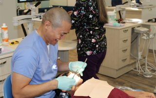Photo of Toothbrushery.com Founder Patricio Andres as he smiles and works on a pediatric patient at Sweetwater Pediatric Dentistry.