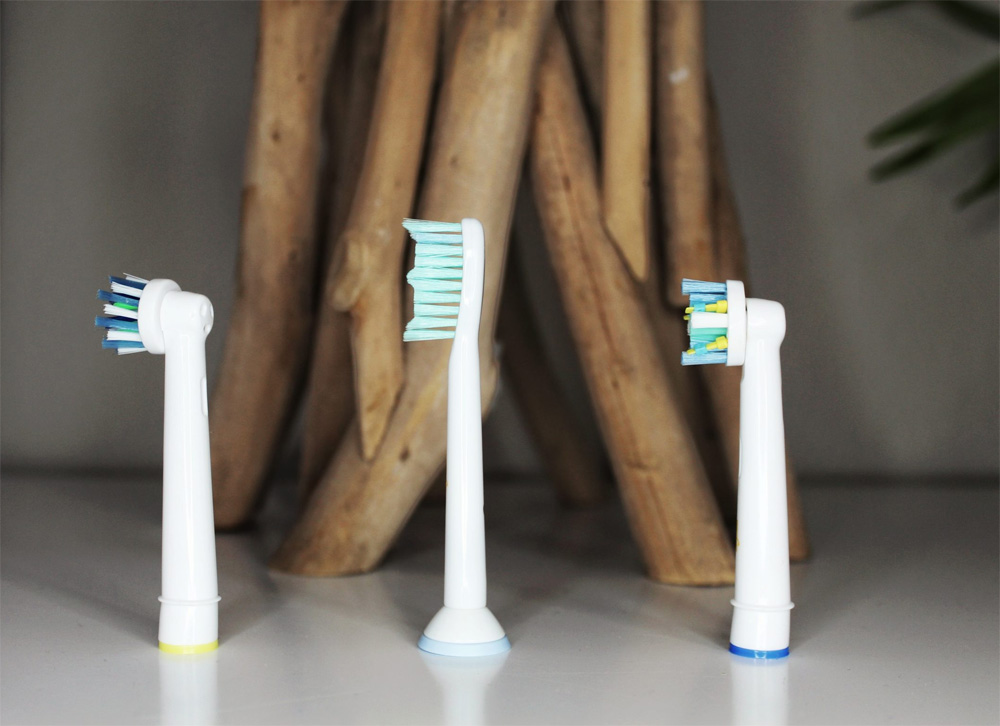 Closeup of three Toothbrushery.com brush heads, standing upright in front of an organic, wooden sculpture that is slightly out of focus. Try our tooth brush subscription service for free.