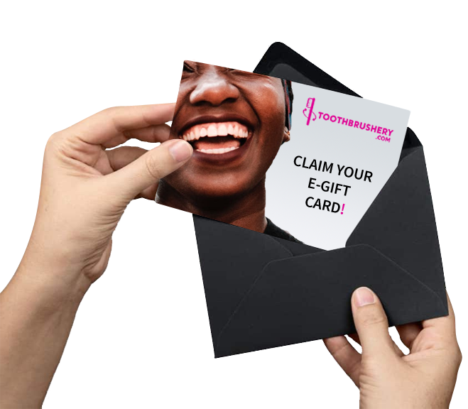 "Promo photo of two hands pulling a piece of paper out of a black envelope that shows a woman smiling and text that reads ""Toothbrushery.com Claim Your E-Gift Card!"". Toothbrushery.com has great toothbrush gift ideas."